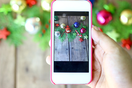Woman hand are holding the phone to take photos of Christmas decorations