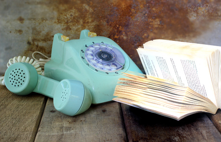 Green vintage telephone and open book on wooden table