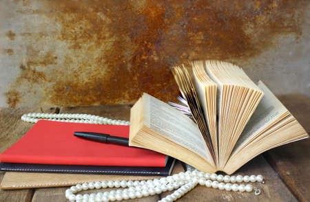 Old open book and red notebook on wooden table