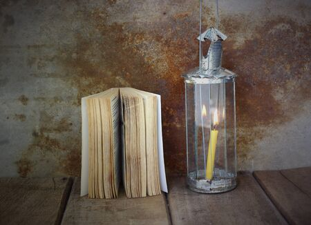 Old book and vintage lamplight on wooden table Stock Photo