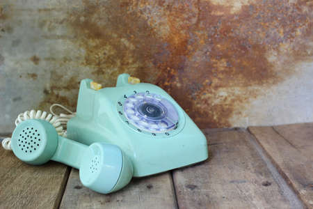 Green vintage telephone on wooden table