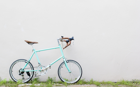 soft pedal: Road bicycle on grass roadside with wall background. Vintage. Soft color. Exercise sport concept.