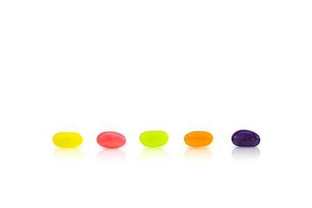 Color jelly beans are lined up in rows on white background. Conceptual sort by order. Stockfoto