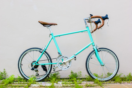 soft pedal: Road bicycle on grass roadside with wall background. Vintage. Soft color. Exercise sports concept.