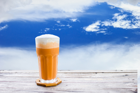 Thai tea frappe (Cha-Thai) on wood table with clouds and sky background. Conceptual tea time for relaxing Stock Photo