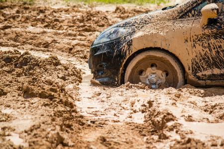 泥の中で立ち往生している黒い車を閉じます。泥から落ちることができません。 写真素材