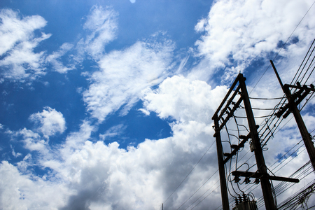 Silhouette electric pole with blue sky and clouds background. Copy space.