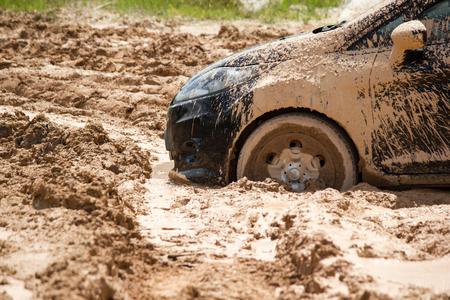 Frente de neumático de coche atrapado en el fondo de barro.