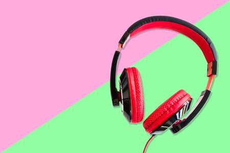 Red and Black earphones on pink and green background.