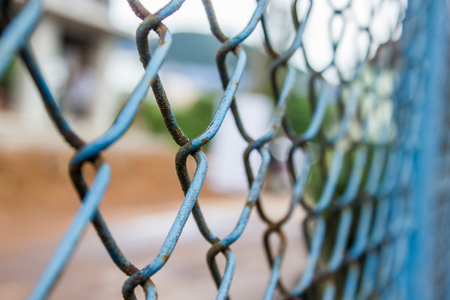 Close up old rusty blue chain link fence. Metal mesh. Selective focus Stock Photo