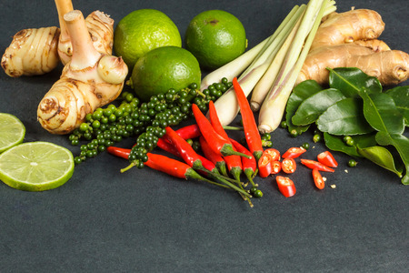 Fresh raw vegetables background. Healthy food ingredient. Thai vegetable background with  Lemon, chili, galangal, lemongrass, pepper, kaffir lime leaves on black tablecloth.