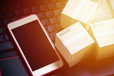 Online-Shopping-Konzept E-Commerce-Lieferung Kaufservice. quadratische Kartons, die auf Laptoptastatur einkaufen und Kundenbestellung über das Internet und das Smartphone anzeigen.