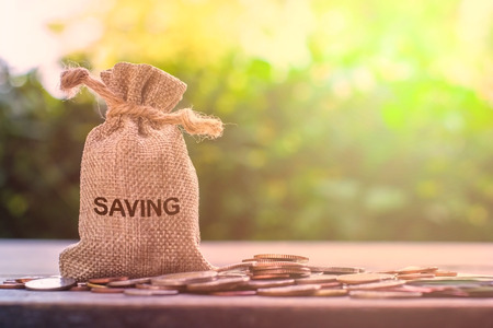 Saving money for future, home, car, education, investment, descendants concept : Money bag with many coins on wood table with green nature and light as background. Copy space for your text.