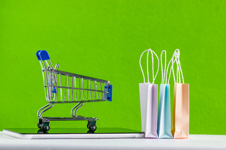 Online market place, eCommerce and delivery concept : Shopping cart on smartphone or tablet with shopping bags on green background.Ordered by customer through the media via internet show that trading.