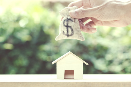 Saving money, home loan, mortgage, a property investment for future concept : A man hand putting moneybag over small residence house and with green nature background. A sustainable investment.