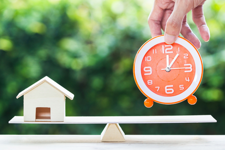 Home bargain, real estate, loan, house lender reverse mortgage concept. Balance orange clock and hand holding small residence on wooden table and blurred green nature as background. Time and home.
