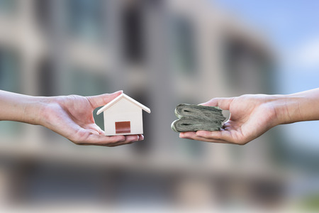 Home loan, mortgages, debt, home buying concept. Hand holding small resident exchange money on blurred real estate background. Exchange of finances and houses.