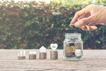 Savings money for family life concepts. Hand holding coin on a full money in glass jar and family member, car, house, healthy on coins. Depicts saving for wealth and life. fundraising concept.