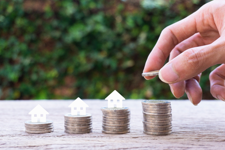 Property investment, home loan, house mortgage, resident financial concept. Stacking coins in 1 to 4 step with small house papercut on coin with nature background. Demonstrate growth of real estate.