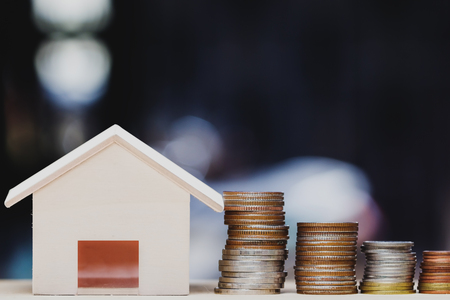 Property investment, home loan, house mortgage, resident financial concept. Stacking coins in 1 to 3 step with small house on table over green nature background. Demonstrate growth of real estate.