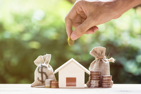 Saving money, home loan, mortgage, a property investment for future concept. A man hand putting money coin over small residence house and money bag with nature background. A sustainable investment. 版權商用圖片