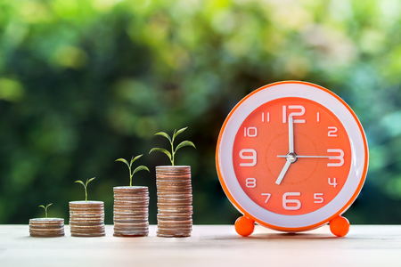 Savings and management money, Money investment for life retirement in the future concept. Plant growing on stack of coins step by step and clock, Depicts financials that grow continuously over time.