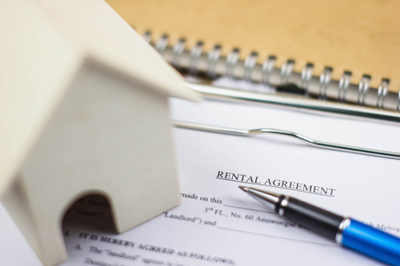Home model and rental agreement document with pen. Depicts the lease contract process for legal validity.