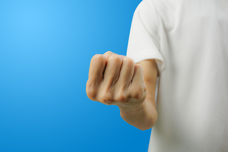 A white shirt man showing fist with his hand front view on blue background. Carefully cut out by pen tool and insert clipping path. Reklamní fotografie