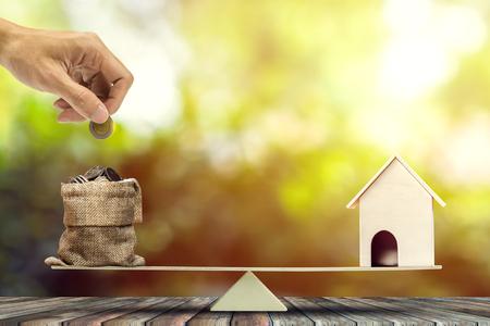 Investissement immobilier, prêt immobilier, hypothèque inversée, épargne pour acheter des concepts de maison. Modèle en bois de maison, main mettant la pièce dans des sacs à l'échelle de la balance en bois. représente un financement pour l'investissement immobilier.
