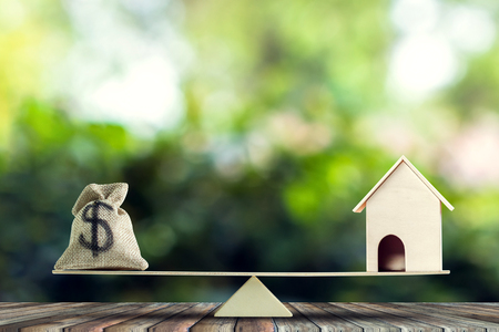Change home into cash concept. US Dollar in sack bag, Wooden house model put on scales on wood table with green tree bokeh as background. Balance home and debt.