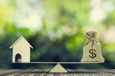 Money and home,loan,mortgage. Change home into cash concept. US Dollar in sack bag, Wooden house model put on scales on wood table with green tree bokeh as background. Balance home and debt.