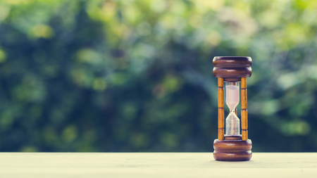 The time concepts. Hourglass on wooden table with green nature background and space at the left. Business countdown to a deadline concepts. Depicts our time is steadily decreasing. Saving a times.