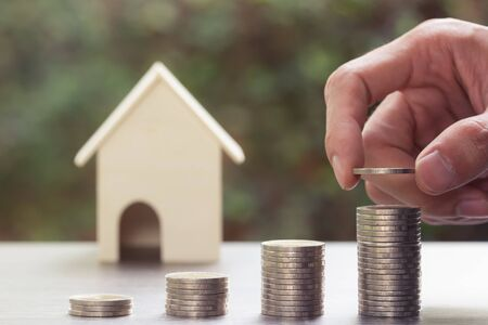 a property investment for future concept. A man hand putting money coin into growing stacked coins with blurred small house. A sustainable real estate investment. Standard-Bild