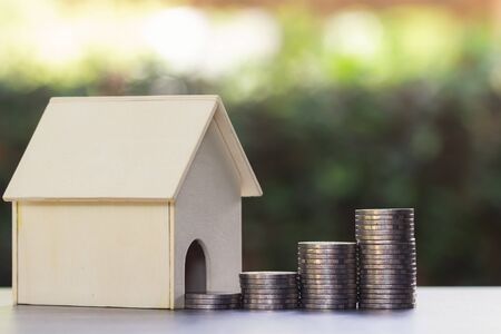 Property investment and home financial mortgage concept. The money flows out of the house on wooden table with nature background. Depicts  house investment Or real estate that grows continuously.