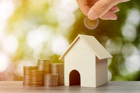 a property investment for future concept. A businessman hand putting money coin over small residence house and stacked coins. Depicts a sustainable investment.