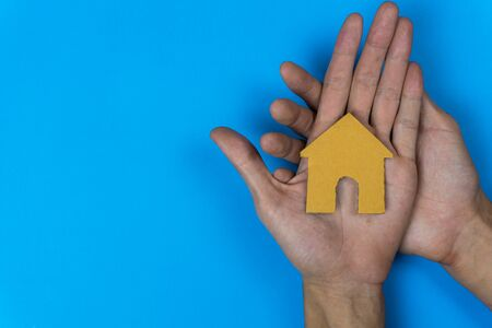 Buy or rent. A small house model made by paper cut on a man hand on blue background.