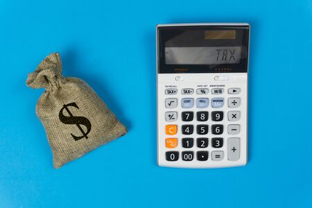 Business and finance taxes concept. A money bag and calculator with text on blue background from top view. Depicts the importance of management about tax, person or company.