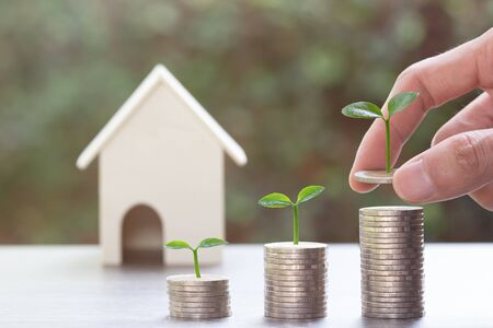 Saving money or property investment concept. A man hand putting coin into rising stack of coins with plant on pile coin on wood table with a small house model. Depicts sustainable financial goal.