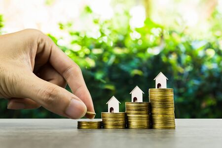 Property investment, savings money for buy new home concepts. A small house model on stack of coins with nature background,Depicts a lasting and long-term investment. Home loan, mortgage, real estate.