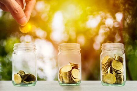 Money savings, investment, making money for future, financial wealth management concept. Hand holding coin over stacked coins in glass jar and growing plant and light. Depicts fund growth and wealth. Stok Fotoğraf