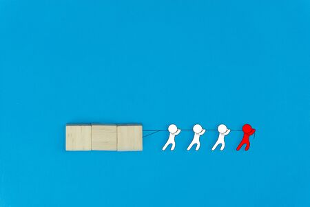 Business leadership and teamwork concept. Leadership help his followers to work tirelessly. Red cartoon character help his team drag a wooden on blue background. Differences between leaders and boss. Stok Fotoğraf