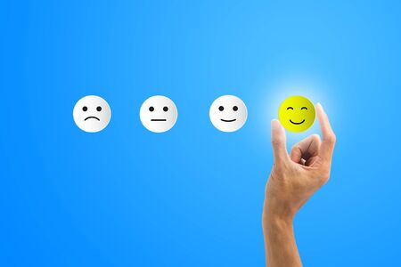 Conceptual the customer responded to the survey. The client using hand choose happy face smile icon on blue background.Depicts that customer is very satisfied. Service experience satisfaction concept. Stok Fotoğraf