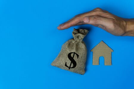 Home insurance concepts. House protect. A man hand protected a small house and money bag over a roof on blue background. Zdjęcie Seryjne - 128111577