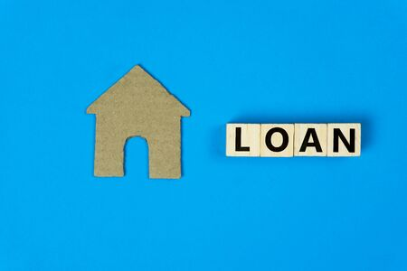 Home loan concept. A small house model made by paper cut with wooden block on blue background. Depicts loans for the build or purchase of new homes. Stok Fotoğraf