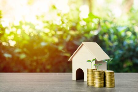 Property investment, savings money for buy new home concepts. A small house model with plant growth on stack of coins. Depicts a lasting and long-term investment. Home loan, mortgage, real estate. Stok Fotoğraf
