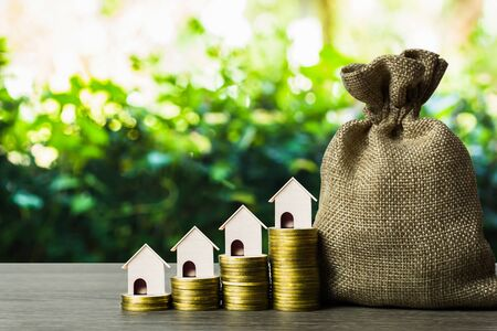 Long-term property investment concept. Home loan, mortgage reverse. Saving money for buy new home. A small house on stack of coins and money bag on table. Depicts investing in sustainable real estate.