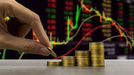 Stock market or business and finance concept. A business man hand holding coin over stack of coins with stock or forex graph. Depicts financial investment.
