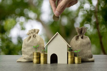 Saving money, home loan, mortgage, a property investment for future concept. A man hand holding coin over a small house and plant growth on stack of coins and money bag. A sustainable investment.
