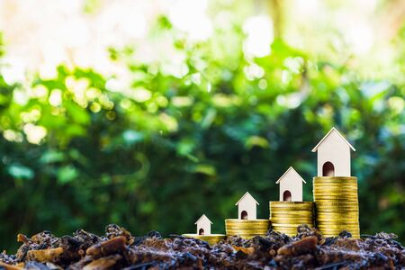 Long-term property investment concept. Home loan, mortgage reverse. Saving money for buy new home. A small house on stack of coins on good soil. Depicts investing in sustainable real estate.