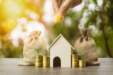 Saving money, home loan, mortgage, a property investment for future concept. A man hand putting money coin over small residence house and money bag with nature background. A sustainable investment. Stok Fotoğraf